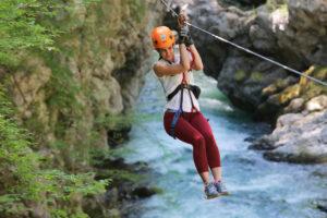 Una ragazza è sospesa in volo tra canyon e rapide sulla Zip Line di Canyon Park